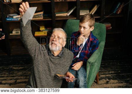 Caucasian Cheerful Bearded Gray-haired Grandfather With His Grandson Enjoy Memories Watching Family