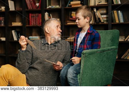 Handsome Bearded Gray-haired Grandfather With His Cute Grandson Having Fun Looking At An Old Photo A