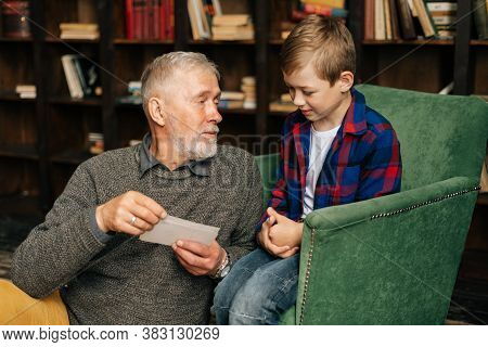 Portrait Of Happy Bearded Grandpa Talking With Cute Grandson, Having Fun Looking At An Old Photo Alb