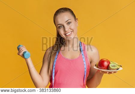 Weightloss Concept. Portrait Of Happy Young Woman Holding Dumbbell And Plate With Fruits And Posing