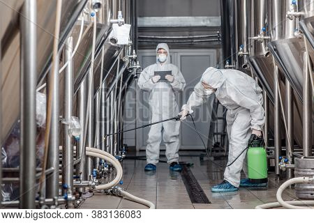 Product Quality, Factory Cleanliness And Disinfection. Men In Hazmat Suits Work With Spray Bags In B