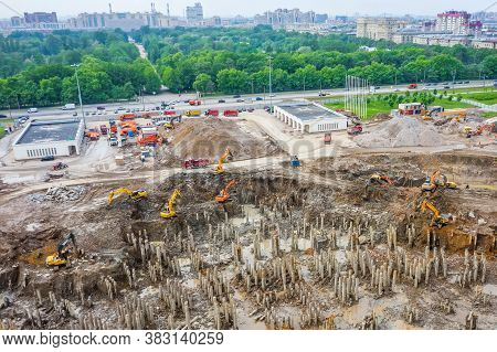 Working Excavators On The Site Of A Demolished Building. Construction Of A Huge Building In A Pit Ne