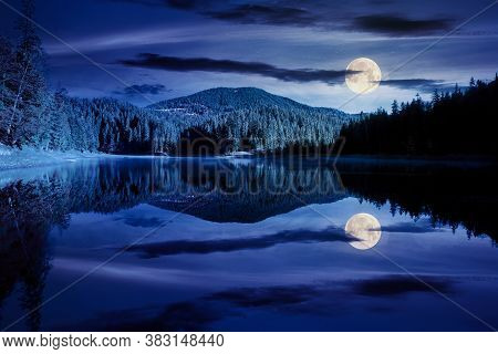 Mountain Lake Among The Forest At Night. Trees In Colorful Foliage. Beautiful Landscape In Autumn Fu