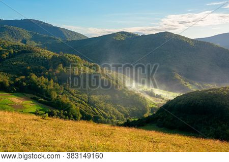 Mountainous Rural Landscape In The Evening. Fields On Hills Among The Forest. Smoke Or Mist In The V