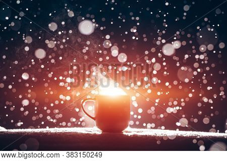 Backlighted Cup Of Hot Steaming Coffee Drink Or Tea On Night Snowy Background