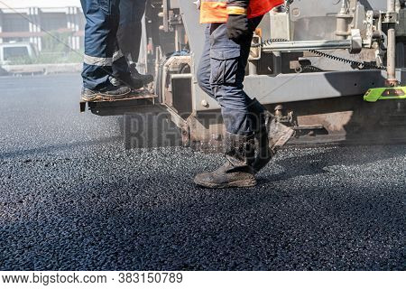 Workers Are Laying New Asphalt, Feet In Heavy Boots
