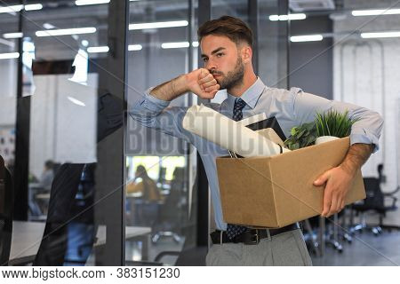 Sad Dismissed Worker Is Taking His Office Supplies With Him From Office.