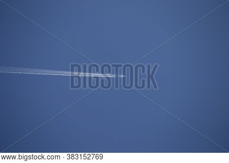 A Passenger Plane Flies High In The Sky, Leaving A Contrail Behind It