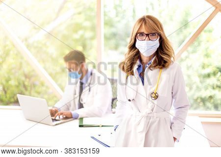 Shot Of Medical Team Working Together In Doctor's Office. Female Doctor Sitting Behind Her Laptop Wh