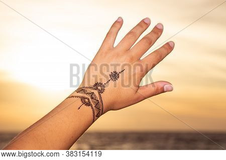 Henna  Tattoo Painting On The  Hand On The Sunset