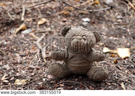 Old Dirty Teddy Bear Neglected On The Ground Soil. End Of Childhood.