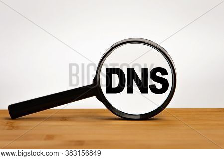 Focused On Business Concept. Magnifier Glass With Text Dns On Wooden Table In Sunlight. Business Con