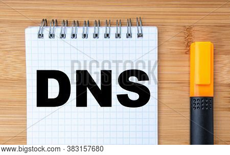 Business Concept. On The Wooden Table Is A Marker And A Notebook With The Inscription Dns Domain Nam