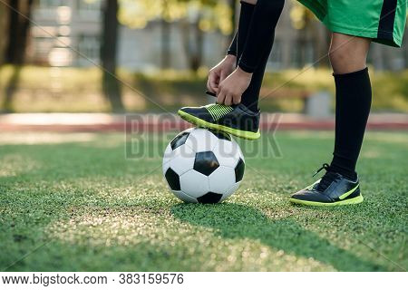 Close Up Boot Of Football Player Which Puts His Leg On Ball And Tying Shoelace On Soccer Stadium On