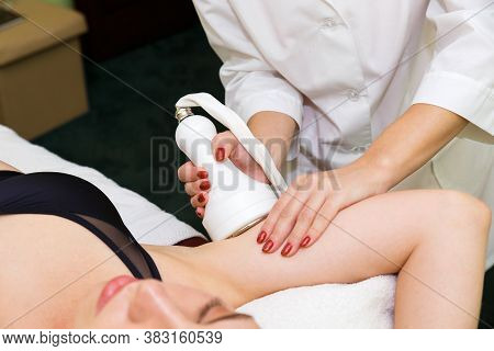 A Young Woman In An Anti-cellulite Procedure In A Massage Parlor. Anti-cellulite Massage Of The Hand