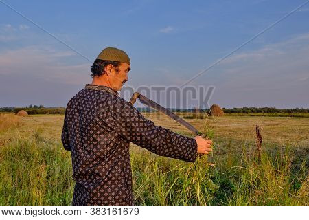 An Senior Asian Man In A Skullcap And Traditional Clothes Cleans A Hand Scythe With Grass In A Hayfi