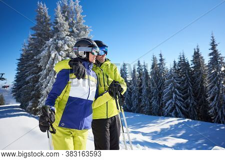 Skiers Lifting On Top Of Slope. Cropped View Of Happy Couple Embracing And Enjoying Winter Views And