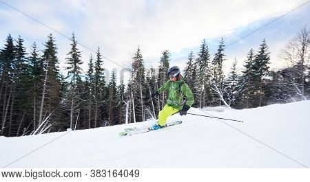 Panoramic Side View Of Fast Risky Skiing On Mountain Slope. Young Male Skier Making Extremal Carving