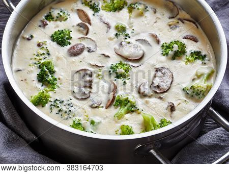 Mushroom Cheese Broccoli Soup In A Pot With Ingredients At The Background, View From Above, Close-up