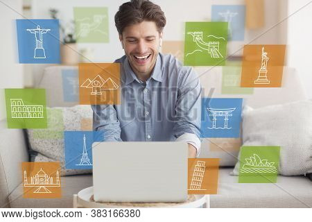 Online Sightseeing Tour. Happy Man Using Laptop Computer Browsing Travel Destinations Sitting At Hom