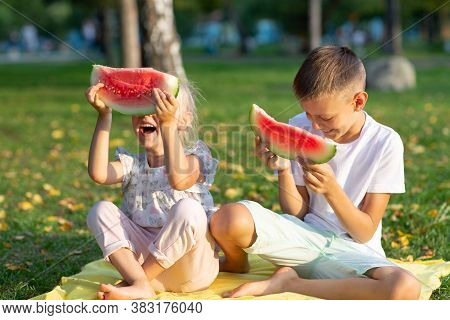 To Cute Kids Lttle Boy And Girl Eating Juicy Watermelon In The Picnic At Autumn Park Meadow
