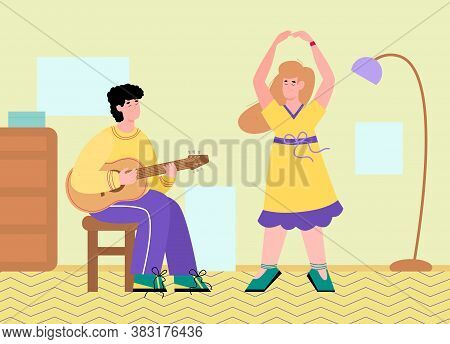 Young Man Sitting On Chair Playing Guitar And Woman Dancing Next To Him. Guy Doing His Favourite Hob
