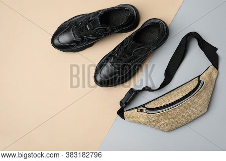 Stylish Black Sneakers And Fanny Pack On Color Background, Flat Lay. Space For Text