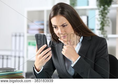 Suspicious Executive Woman Checking Smart Phone Sitting On A Desk At The Office