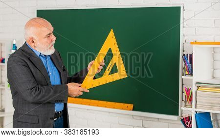Maths Problem Solving. Senior Man Teacher Use Math Triangle Tool. Bearded Tutor Man At Blackboard. B