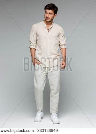 Trendy Look. Full Length Of Handsome Young Man Looking Away And Keeping Hands In Pockets While Stand