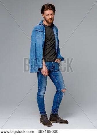 Full Body Of A Fashion Man Holding His Jeans Shirt By Its Collar