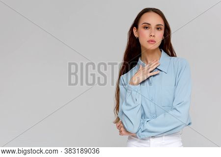 Close Up Portrait Of Serious Young Woman In Blue Shirt Looking At Camera, Isolated On Gray Backgroun