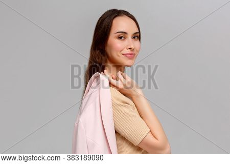 Portrait Of A Young Beautiful Cute Funny Girl Smiling Looking At The Camera Holding A Jacket In Her