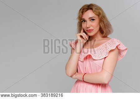 Portrait Of Beautiful Casually Dressed Young Caucasian Woman Having Doubtful Expression, Looking Awa