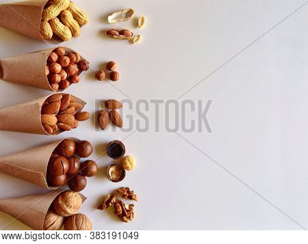 Different Nuts Source Of Protein On A Light Background Close-up. The Concept Of Healthy Proper Nutri