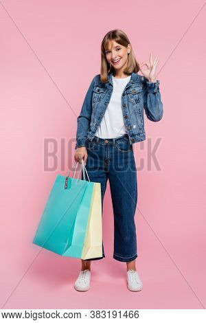 Young Woman With Shopping Bags Showing Okay Gesture On Pink Background