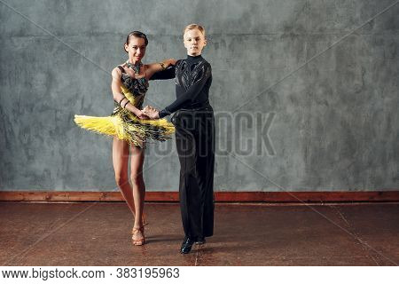 Young Man And Woman Dancers Dancing In Ballroom Dance Cha-cha-cha.