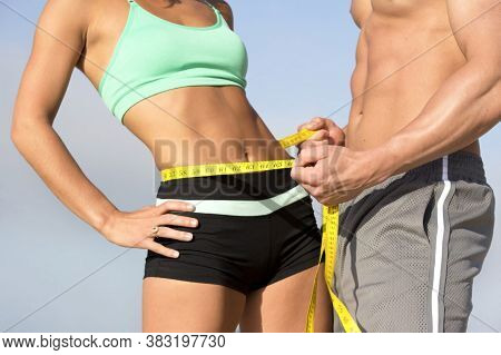Torso of fit couple in sports wear with muscular physique as weight loss concept