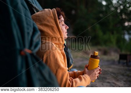 A Serene Caucasian Woman Sits Alone In A Tourist Tent Drinking Hot Tea From A Thermos. The Girl Enjo