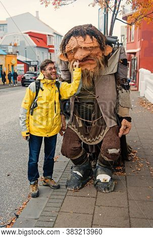 Reykjavik, Iceland - October 12, 2017: Man Tourist Picking Nose Of Troll Figure. Happy Man With Clay
