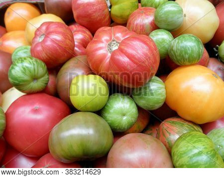 Pile Of Multi-colored Heirloom Tomatoes On Display At A Farmers Market.