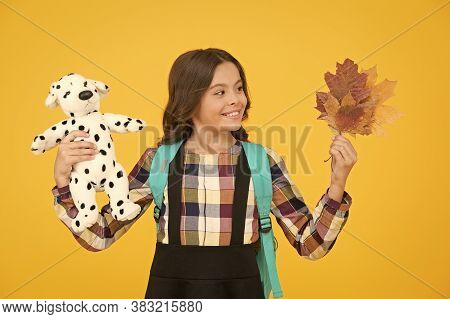 Little Schoolgirl With Toy Backpack And Leaves. Happy Childhood. Beginning Of Academic Year. Autumn