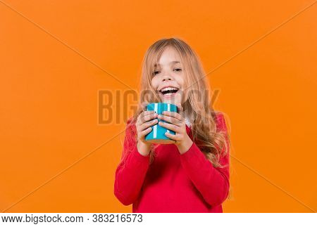 Tea Or Coffee Break. Child Smile With Blue Cup On Orange Background. Girl With Long Blond Hair In Re