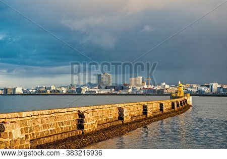 Lighthouse On Sea Pier In Reykjavik Iceland. Lighthouse Yellow Bright Tower At Sea Shore. Seascape A