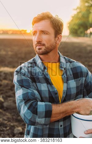 Rancher In Plaid Shirt Looking Away While Standing On Field With Bucket