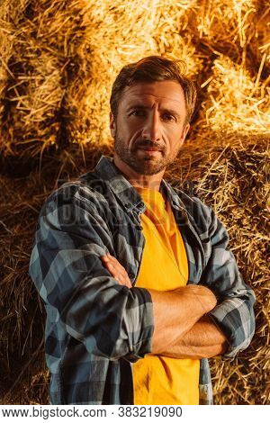Rancher In Checkered Shirt Looking At Camera While Standing Near Hay Stack With Crossed Arms