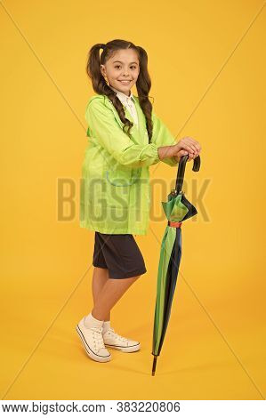 Small Girl In Raincoat With Umbrella. Schoolgirl Waterproof Raincoat. In Good Mood. Feel Protected A