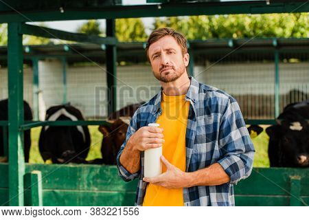 Rancher In Checkered Shirt Holding Bottle Of Fresh Milk While Looking At Camera Near Cowshed