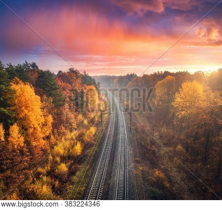 Aerial View Of Beautiful Railroad In Autumn Forest In Foggy Sunrise. Industrial Landscape With Railw
