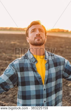 Rancher In Checkered Shirt Looking Up While Standing On Plowed Field
